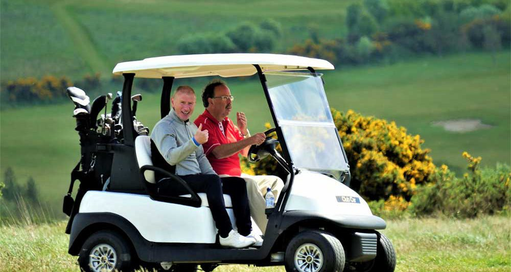 Two golfers in a caddy car on the golf course at the Comis Mount Murray